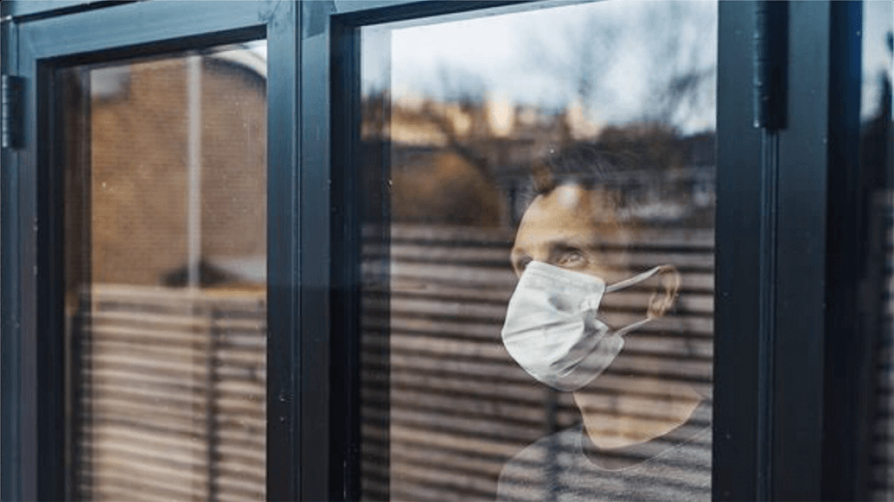 Man wearing a mask looking out window.