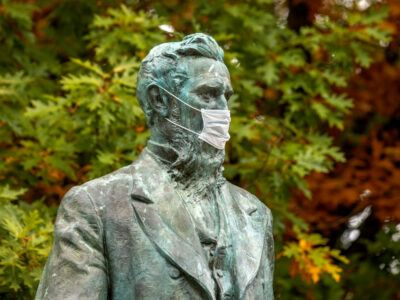 The statue of Ezra Cornell wearing a mask