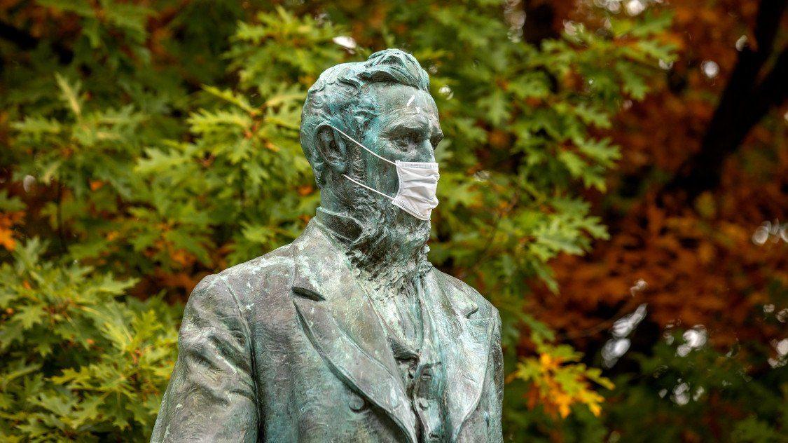 The statue of Ezra Cornell complies with the university's mask mandate. Photo Credit: Jason Koski