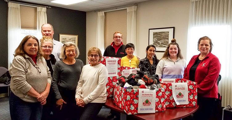 Cornell Club of Ithaca members with a box of donated socks