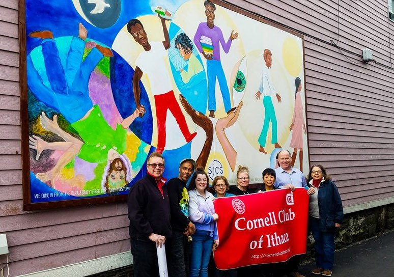 Cornell Club of Ithaca members standing beneath a mural in Ithaca
