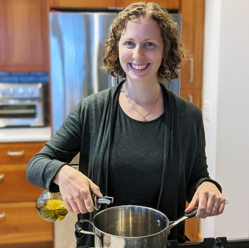 Nutritionist Erin Harner pouring extra virgin olive oil in a pan to make soup.