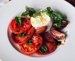 One of Blake's favorite culinary creations using his homegrown produce: Cherokee Purple, Mortgage Lifter, and Black Prince heirloom tomatoes, burrata, and flowering basil