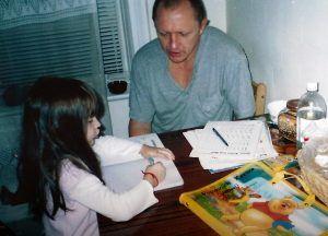 Karina's grandfather, Vasyl Rudeychuk, helping her with her math homework