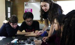 Karina in high school, working with a group of students to 3D print toys for kids at the Ronald McDonald House.