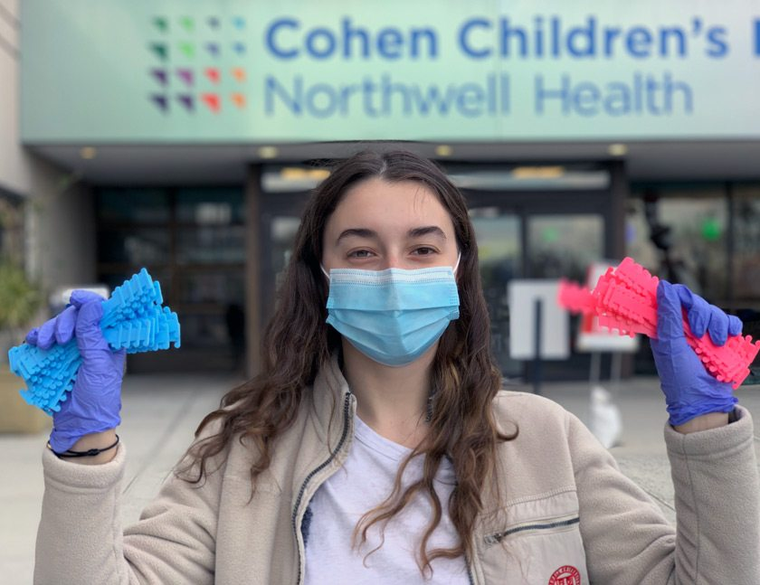 Karina holding ear savers (a type of PPE that relieves pressure from the ears when wearing a surgical mask) that she 3D printed and donated to the Cohen Children's Hospital.